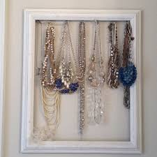 Homemade necklace holder, made with a backless frame and hooks at the top.  Inspired