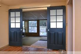 black rolling barn door style doors with six panes of glass of equal size on top