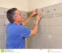 Tile In Bathroom Man Installing Ceramic Tile In Bathroom Stock Photography Image