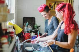 Two Young Women With Pink Hair Laughing Whilst Washing Dishes At