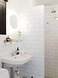 floor to ceiling subway tile bathroom. black and white bathroom features floor to ceiling subway tiled walls as well open shower with tile surround arc rain head. l