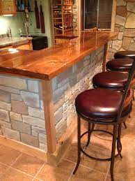 faux stone panels for dining room table design with wood countertop and brown leather stools ideas