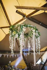 greenery and white flowers on a hoop as a wedding chandelier