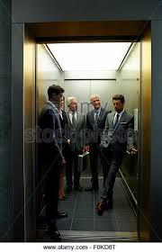 people standing in elevator. group of businesspeople in an elevator - stock image people standing n