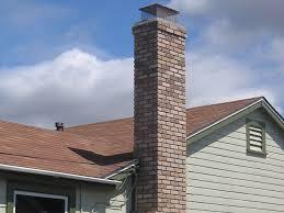 custom masonry brick chimney with brick corbels just below chimney cap and spark arrestor