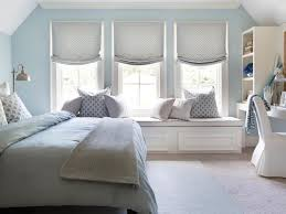 brian patrick flynn blue and gray bedroom features blue walls lined with a beige linen headboard with nailhead trim on bed dressed in blue bedding and a
