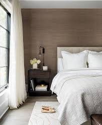 packed with style this modern gray and brown bedroom features an accent wall covered in brown grasscloth and positioned behind a heather gray tufted