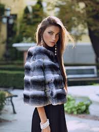 side profile of slender woman wearing a short fur coat jacket and black dress