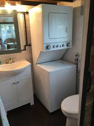 tiny house washer dryer. A Stackable Washer And Dryer Unit Is Tucked Into The Corner Next To Full-sized Toilet. When You Need Privacy, Just Slide Barn Door Between Tiny House D