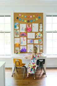 kids art displayed on large cork board wall in home office above kids art  desk