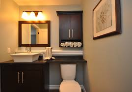 black wall mounted bathroom storage cabinet with towel shelves over toilet beside wooden cabinet under wall mirror and lighting ideas