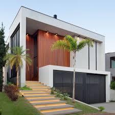 O projeto é composto por três níveis. Fachada De Casa Contemporanea Em Aclive Com Painel De Madeira E Portao Preto De Chapa Perfurada Decor Salteado
