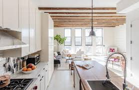 lovely kitchen features white shaker cabinets paired with marble countertops and a white linear tiled backsplash
