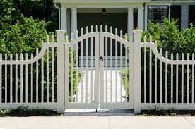 white picket fencing and front gate lead to an elegant home entrance
