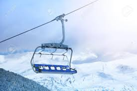 close up of ski lift chair with mountain tops on the background stock photo