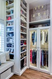 the details in this closet are what make the space the trim work built in window seat and don t forget the lighted wardrobe with glass front doors