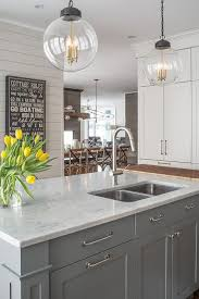 gray kitchen island topped with white quartz fitted with a stainless steel dual sink