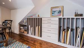 Custom wall unit art storage is fitted under the eaves and sloping roof