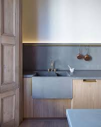 a peaceful minimalist kitchen with light colored cabinets and concrete countertops and a backsplash