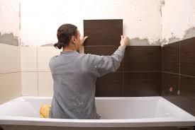 man tiling shower surround