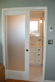 frosted glass pocket door with white painted wooden frame for bathroom with glass closet