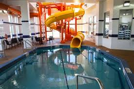 indoor pool with waterslide. Guests Outstanding Accommodations In Spacious Rooms With Modern Amenities Including A Full, Hot Complimentary Breakfast, Two Story Waterslide, Pool Indoor Waterslide