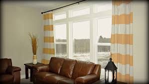 beautiful striped curtains with long curtain and nightlamps also single sofa combined with fluufy rug and
