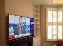 sony tv with ps4. this ultra hd tv was installed on a flat wall bracket above the working fireplace cables were chased to side cupboard which housed sky box and sony ps4 tv with ps4