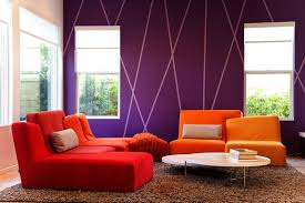 purple accent walls white wall windows orange and red couches brown fluffy rug white coffee table