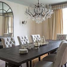 beautiful dining room boasts a white capiz chandelier hanging over a reclaimed wood trestle dining table lined with linen dining chairs with nailhead trim