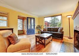 cozy living room with fireplace. Cozy Living Room Interior With Warm Yellow Walls , Fireplace And Hardwood Floor. Northwest,