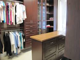 mahogany sizable closet incorporates square raised panel drawers doors glass enclosed shoe shelving and a lovely center island topped with granite
