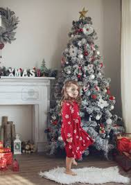 Young Boy And His Pet Dog Sitting Looking At Their Christmas Tree At Home Christmas Tree