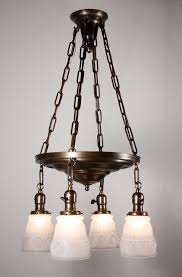 this is a fabulous antique four light brass chandelier dating from the 1920 s with original glass shades the chandelier begins with a brass canopy