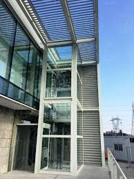 Steel brise-soleil canopy and laminated glass elevator shaft