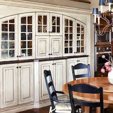 full custom kitchen with distressed painted wood cabinets with glass front doors