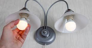 a hand ing in an led light bulb into a fixture