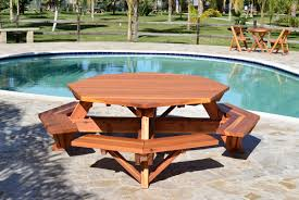 outdoor octagon wooden picnic table with benches beside pool with stone floor tiles ideas