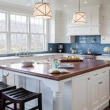 white kitchen cabinets with blue subway tiles