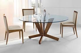 round glass dining table with wooden legs complete with wine and glass plus contemporary dining chairs suitable to complete of furnitures in the