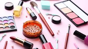 makeup and makeup tools and brushes laid out on a table