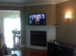 tv mounted over fireplace corner mounted over white fireplace as well as hiding wires for wall