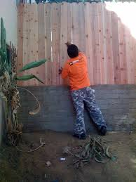 the ultimate handyman installs carpentry fences above retaining walls to complete the looks