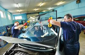 three workers replacing a windshield in an auto glass
