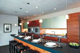 the kitchen in this photograph combines recessed can lights pendant lights and under cabinet