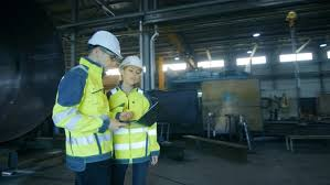 Industrial Engineer In Hard Hat And Safety Jacket Looks Around In