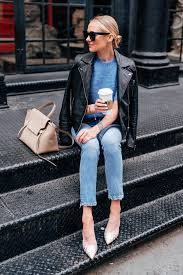blonde woman wearing black leather jacket anine bing nicolette blue sweater denim skinny jeans snakeskin mules