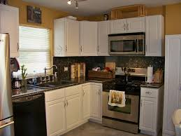 small kitchen design with white l shaped kitchen cabinet and grey granite top also white blinds