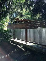 neighbor building fence on property line neighbor building fence on property line corrugated metal and wood fence with horizontal slats just add