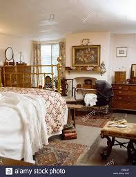 Rose patterned quilt on antique brass bed in Victorian style ... & Rose patterned quilt on antique brass bed in Victorian style bedroom with  vintage dolls pram Adamdwight.com